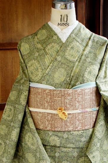 生成り色とオリーブグリーンやグラスグリーン、モスグリーンなどの味わい深い様々な緑で、ヨーロッパの紋章のようなサークルモチーフと、格子窓のようなチェック模様が織り出された、正絹紬の単着物です。