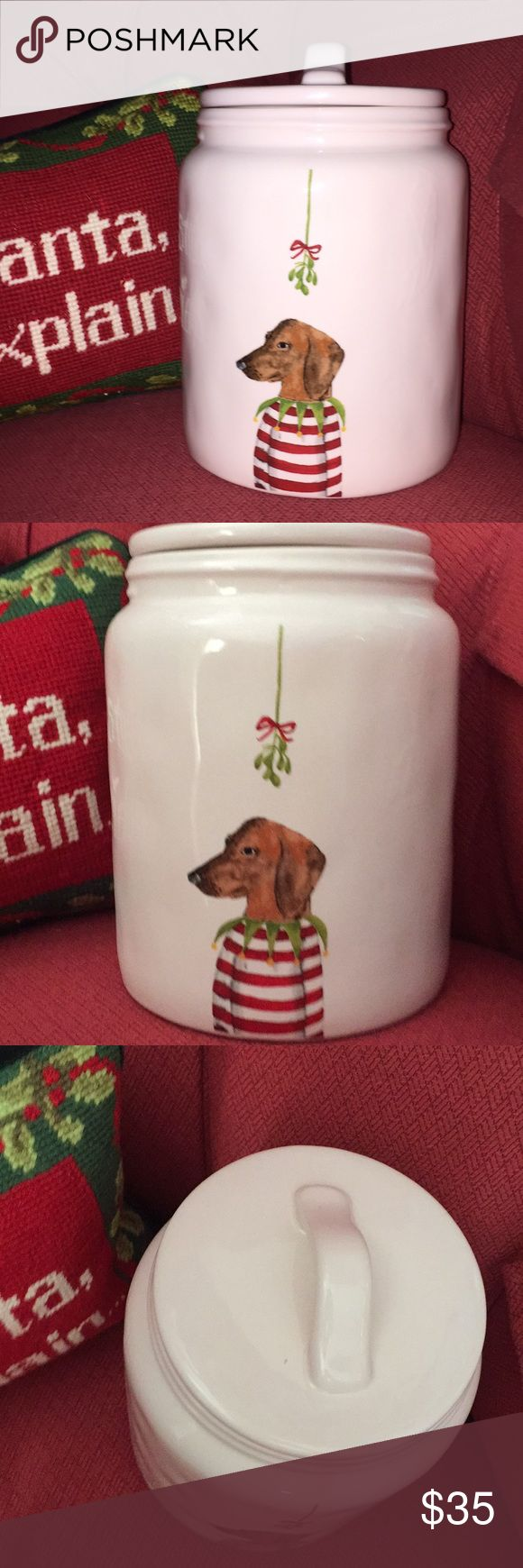 NEW! RAE DUNN WHIMSICAL COOKIE JAR NEW!! Authenticity Rae Dunn Artisan Collection by Magenta. NEW!! Classic creamy white Rae Dunn background. Cookie Jar Decorated with a detailed dog dressed as an elf on the front with a candy cane striped shirt and a green with jingle bells collar. Mistletoe  above him  hanging by a red bow ribbon. Large lid with rubber gasket to ensure closure. Back of the jar / canister is blank and can be turned around for a plain look.  Rae Dunn Other