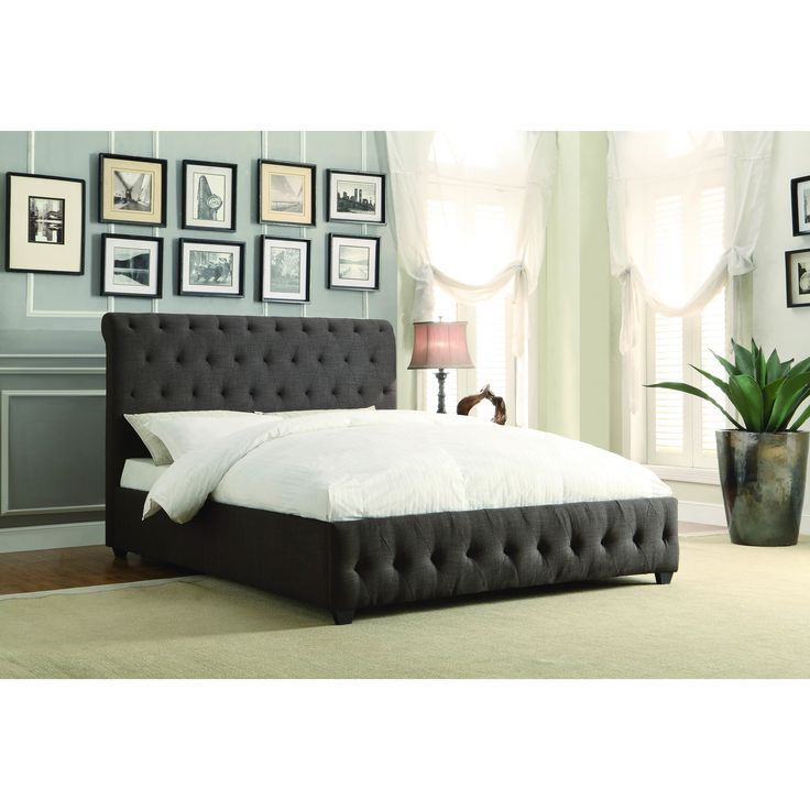 A rolled and tufted headboard provides elegant