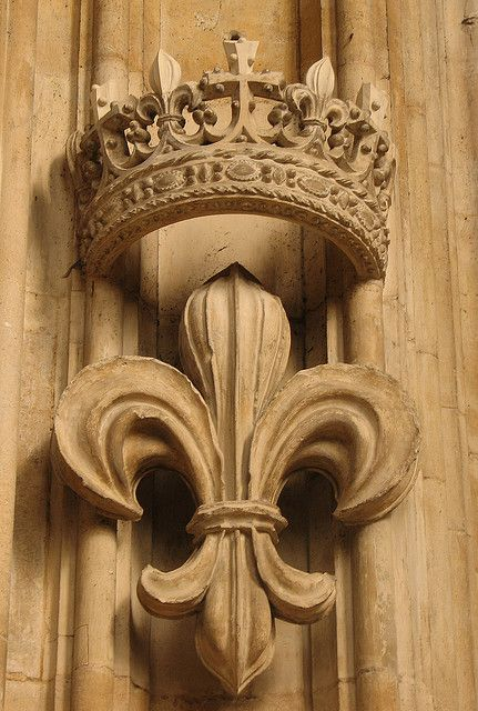 The fleur-de-lis, identified as a lily by the Council of Trent (1545) was first encountered as an emblem of French royalty in the reign of Louis VII (1120-80).  When Edward III of England, whose mother was Isabella of France, began to claim the throne of France for England's kings, the fleur-de-lis began to be used in the Royal Arms of England.  They feature as one of the royal emblems on the arms of King's College, Cambridge, and are found all over the chapel.