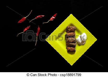 Romanian cuisine - Plate with sarmale, Romanian traditional dish consisting in rolls of ground meat and rice wrapped in vine leaves and served with yogurt. Overhead shot, isolated on black background.