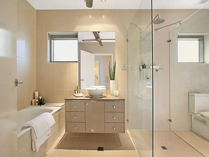 Cream-colored and revealing a simple design, this modern bathroom displays an…