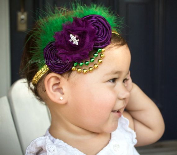 The Mardi Gras- Purple Rosette Flowers and Green Feathers Accented with Mardi Gras Beads on a Gold Glitter Elastic Headband