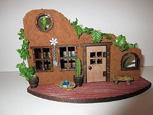 Fairy Garden Miniature Southwest Adobe Hacienda OOAK Fairy Garden Accessory. This sweet little adobe hacienda will add a flair of the southwest to your garden. It would also look cute in a western setting. The house is made of wood, stained, and painted with adobe texturing. The front porch is adorned with pots, a vine, a cactus, a tiny bench and a basket of faux turquoise. There is also a small wind chime hanging on the front wall with faux turquoise and beads. Around the front wall is a...