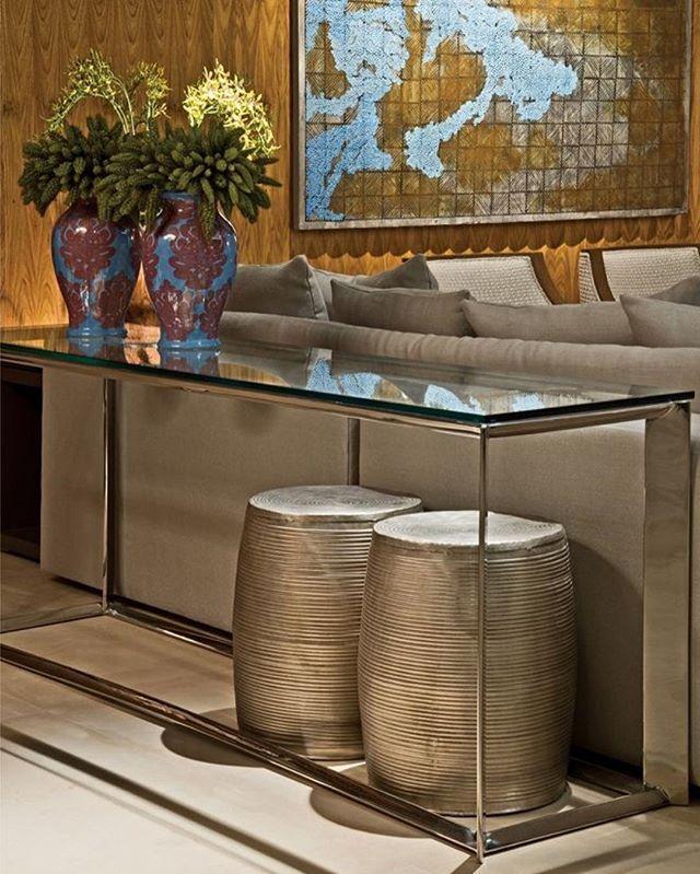 Adoro a ideia de usar um móvel na parte de trás do sofá, quando ela fica aparente. Nesse projeto, um aparador em aço inox polido e dois gardens em alpaca foram utilizados.