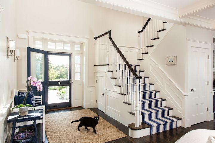 entry design w/navy blue door; navy & white striped stair runner