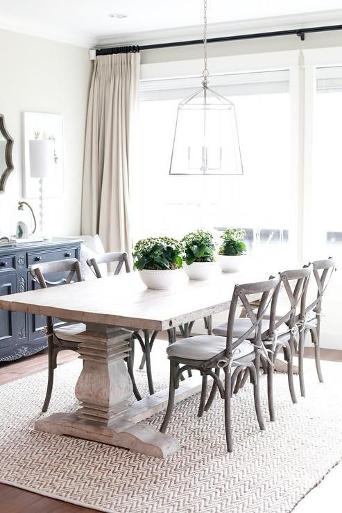 In Front Of Windows Dressed In Cream And White Banded Curtains Hung From An Oil Rubbed Bronze Curta Cottage Dining Rooms Farmhouse Dining Room Farmhouse Dining