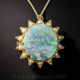 A unique and intriguing late-Victorian jewel glows  with an absolutely stunning and unusual circular-cut Australian opal aglow with a pastel pallet of rainbow hues. The resplendent gemstone is framed by 14 pearl-set sun rays. There is a virtually invisible fissure running trough the gemstone and we have discounted the piece accordingly. Wearable as both a pendant or pin. A truly lovely  adornment.