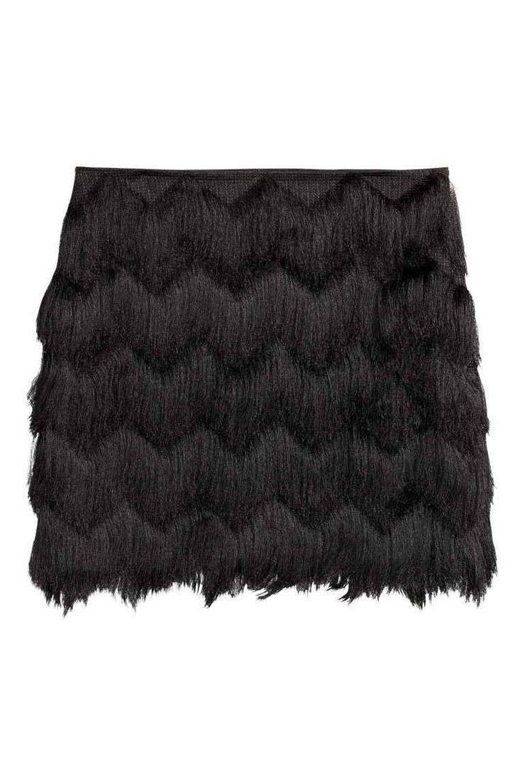 Rok met franjes: Een korte rok met een zigzagdessin van franjes, een zichtbare ritssluiting achteraan en een voering van tricot.