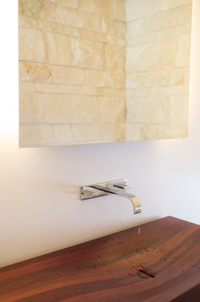 Mr. Dunbar also wanted a home that would fit in his native Australia. The dark wood panels used on floors, the exterior of the house and this custom-made sink are reclaimed Jarrah wood, a type of Eucalyptus imported from Australia.