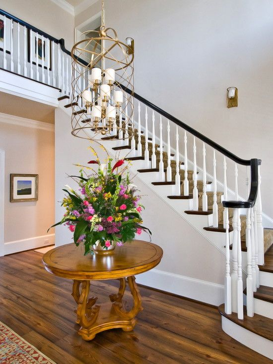 Dark stair rail with white spindles round table in for Foyer staircase ideas