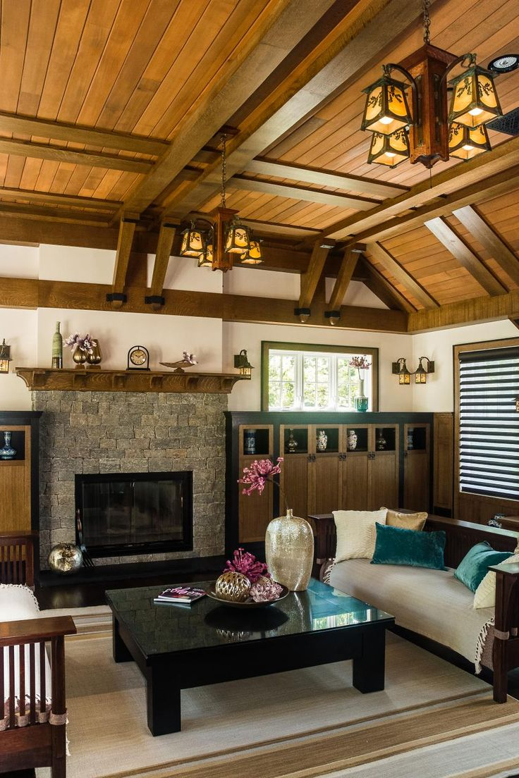 A vaulted exposed beam ceiling with wood planks and wrought iron chandeliers create a craftsman style look for this spacious living room. Two built-in wooden cabinets enclose the stone fireplace, while two sofas and a striped area rug add neutral touches to the space.
