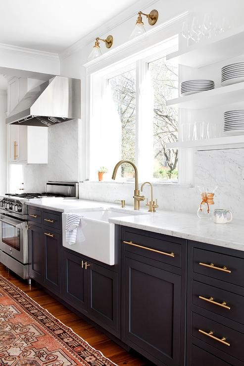 Gorgeous blue and white kitchen boasts navy blue lower shaker cabinets and white upper cabinets finished with long brass pulls and honed white marble counters.