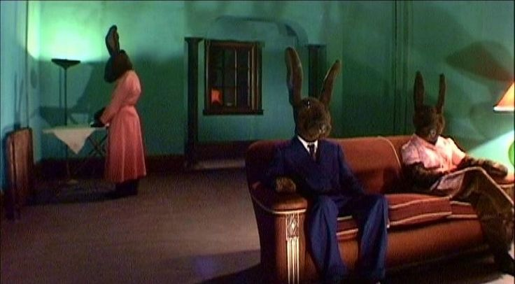 "Rabbits is a 2002 mini-series by David Lynch. Rabbits is presented with the tagline ""In a nameless city deluged by a continuous rain... three rabbits live with a fearful mystery"". In addition, the set and some footage of Rabbits are reused in Lynch's Inland Empire."