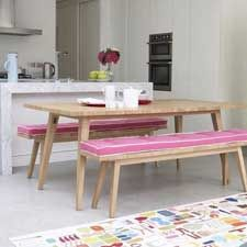 Use benches with a comfy upholstered pillow to provide lots of seating for impromptu dinners in your small apartment.