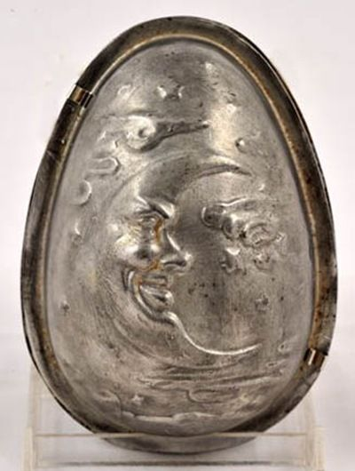 Wonderful chocolate Easter egg mold  with a man-in-the-moon motif.