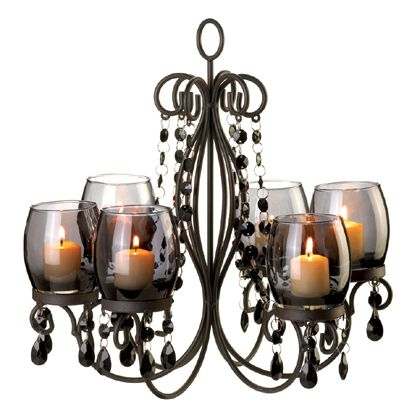 The glow of a sultry evening can be yours whenever you want. This chandelier's faceted baubles dangle and reflect the sparkle of six candles set in tinted glass, creating the perfect ambiance for a romantic getaway right in your own home.