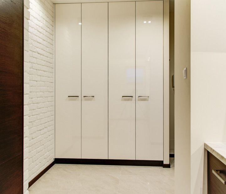 Przestronne i jasne wnętrze przedpokoju z pojemną szafą. Ceglana ściana w przedpokoju.
