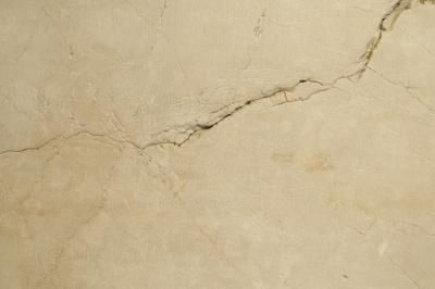 Whether found in drywall, plaster or concrete, a crack in a wall is an eyesore. Generally caused by the natural settling of a house over time, you can repair a cracked wall in a weekend. Simple tools ...