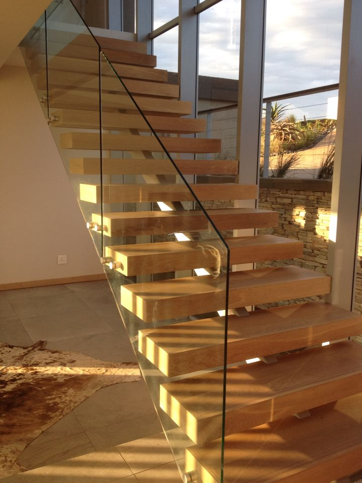 Open stair with timber treads and steel structure beneath, glass balustrade.