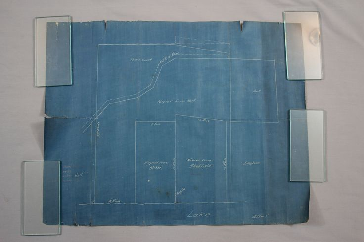 """The before conservation image of a land survey/blueprint plot map. The map had been stored rolled for many years. The exposed edges had tears and the paper had a strong """"memory"""" of being rolled. The paper had also become quite brittle. After being conserved at Spicer Art Conservation, the map was framed using archival materials, including UV filtering plexiglas. The frame was sealed to prevent dust, debris or other contaminants from entering."""