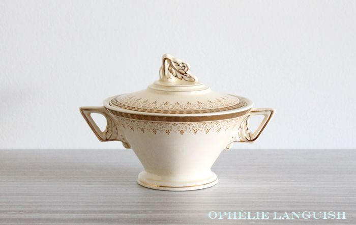 Stunning vintage cream coloured Art Deco sugar bowl and creamer set with classic bold geometric styling and lavish ornamentation. Double handled sugar bowl with gilded leaf motif handle on lid. Footed sugar bowl and creamer with intricate scroll borders. Gold encrusted rims and trim. Rare pattern. Exudes class, luxury, and glamour.