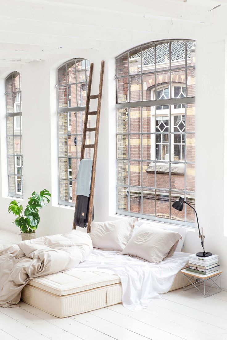 Yumeko sustainable bed linen | industrial building Amsterdam | high ceiling with traditional windows | white bedroom | loft