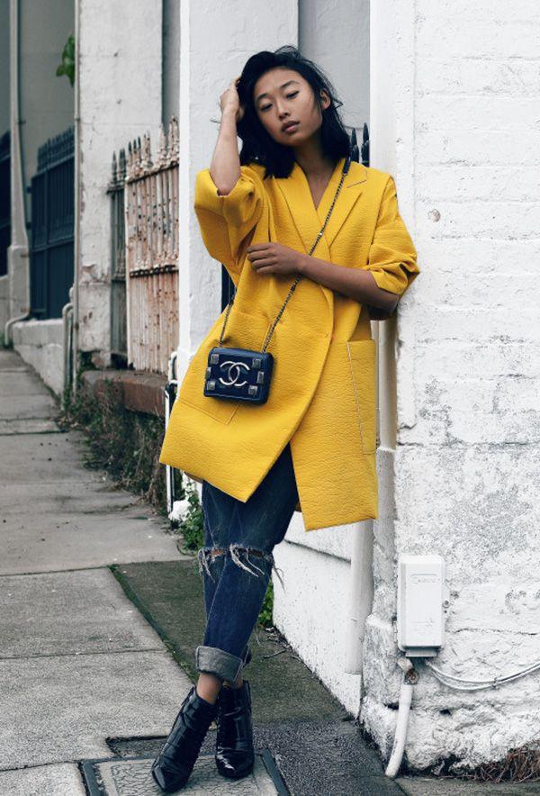 Street style look com casaco amarelo, calça jeans e bota verniz.