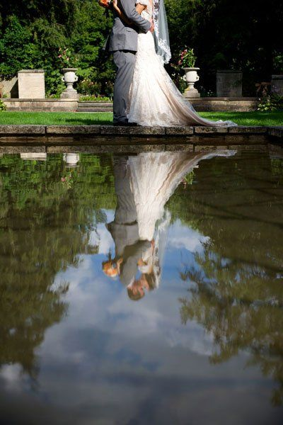 "Why We Love It: A unique twist on a classic picture! We love this innovative idea.Why You Love It: ""Love this because it looks natural. The reflection is amazing."" —Jenn K. ""A reflection of love."" —Trish W. ""Love it! I'm thinking of a picture like this for my wedding this October."" —Mi'chelle L. ""This photo looks like it's straight out of a fairytale! Reminds me of The Princess Bride."" —Linen TableclothPhoto Credit: BTW Photography"