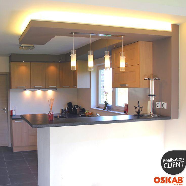 Cuisine ouverte moderne avec bar séparateur, implantation en U, ouvert sur le séjour, meubles de cuisine en bois verni, plan de travail gris, 4 luminaires suspendus au-dessus du bar pour éclairer le plan de travail - www.oskab.com