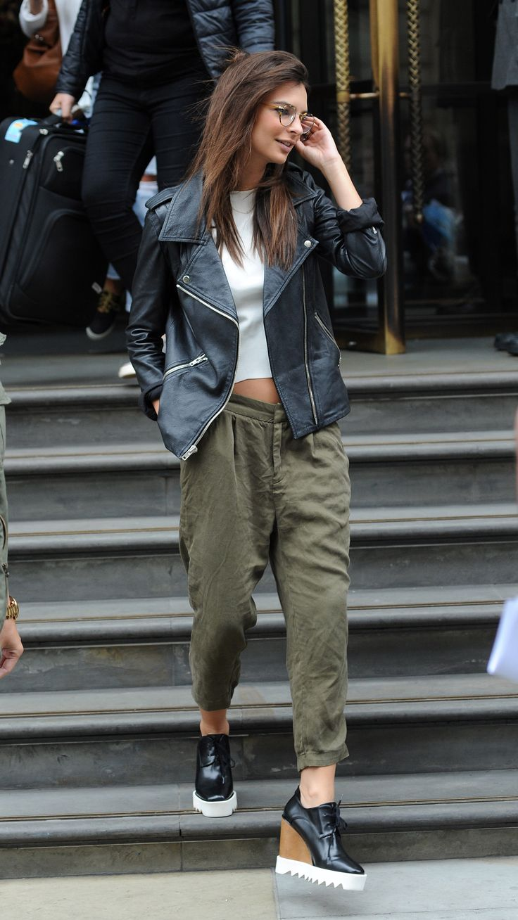 Leaving her hotel in London in platform shoes, a leather jacket, and green cargo pants.   - ELLE.com