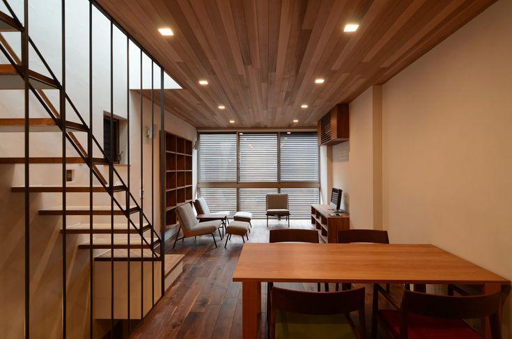 上下を木に挟まれたリビングダイニング。前面ルーバーから光が入る。この写真「ダイニングからリビングを見る。」はfeve casa の参加建築家「植本俊介/植本計画デザイン一級建築士事務所」が設計した「御徒町MK邸<下町に建つ現代版立体町家>」写真です。「三階建住宅 」カテゴリーに投稿されています。