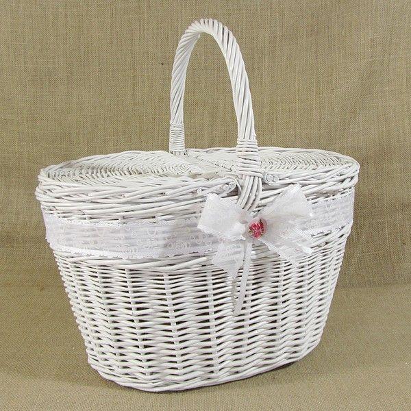 Biały koszyk wiklinowy zdobiony białą wstążką ze wzorem i kokardą