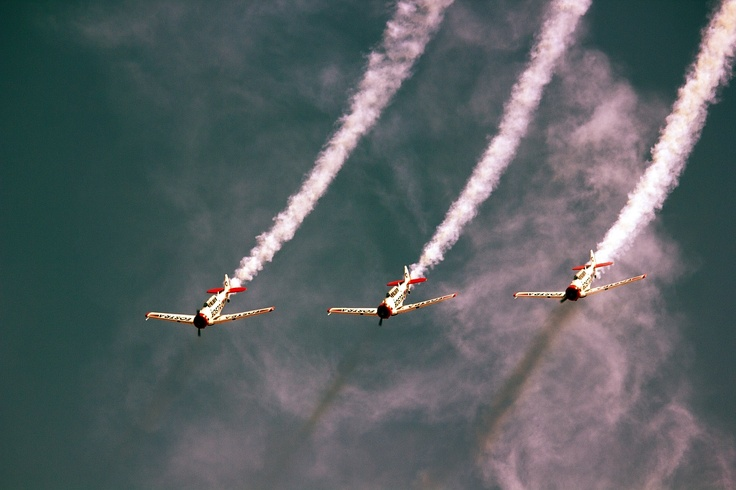 Trick planes gliding through their own smoke after making a complete 360* turn.
