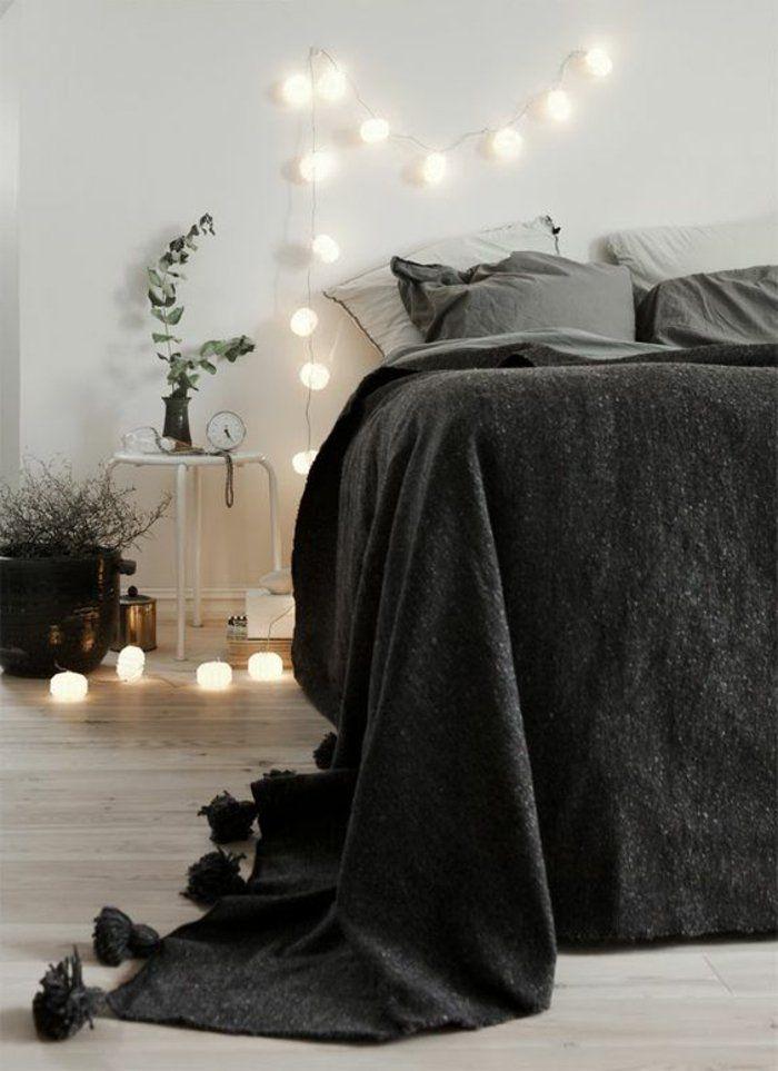éclairage romantique, mur blanc, couverture de lit en gris foncé, sol en parquet clair