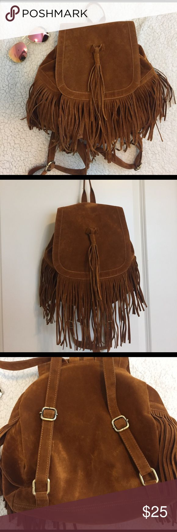 """🌺 Faux Suede Fringe Tassel Backpack Used a handful of times, adjustable straps, 2 pockets, drawstring enclosure with magnetic clasp to secure, small scuffs as shown in last picture. I would say the color is brown with more of an orange-ish tint. Dimensions are approx. 11"""" x 4.5"""" x 13"""". Would not fit a lap top or binders. This is a small bag, but it is perfect for festivals, daily essentials, spring break on the beach, or even a day at DisneyWorld!  Excellent condition. Sad to see this go :(…"""
