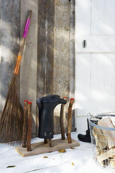Laarzenrek  Nodig: stuk steigerhout • stevige takken van 48,5 cm (ca. Ø 3,5 cm) • boor (diameter van tak) • grote schroeven • fluo verf  Zaag de plank op de gewenste lengte. Hier is hij 62 x 19, 5 cm. Teken af waar de takken moeten komen en boor gaten tot halverwege de plank. Plaats de tak in het gat en zet die vast met een lange schroef vanaf de onderkant van de plank.