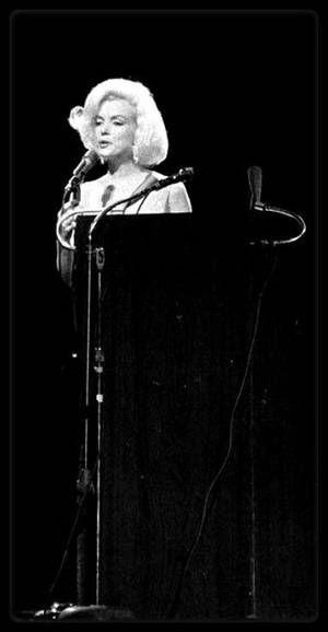 """19 Mai 1962 / Marilyn est conviée au gala d'anniversaire de John F KENNEDY ; Elle est vêtue d'une somptueuse robe de soie (créée par le couturier Français Jean Louis) cousue à même son corps, sous laquelle elle ne porte aucun sous-vêtement, et porte une fourrure d'hermine blanche qu'elle aurait empruntée au département costumes de la Fox (qui ne cautionne pas la venue de l'actrice au Gala de JFK). Une foule de 15 000 démocrates sont venus acclamer les 45 ans de leur président au """"Madison…"""