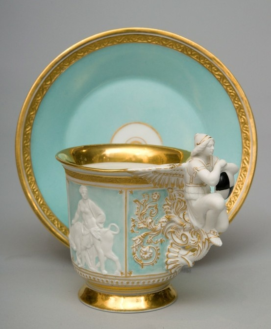 Rare porcelain cup & saucer with an elaborated handle decorated with an angel holding a shield. The sides are adorned with mythological figures on the turquoise ground. Factory of KPM Berlin late 19th century