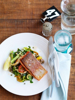 Ocean trout with calamari, cherry tomato and zucchini flower salad.