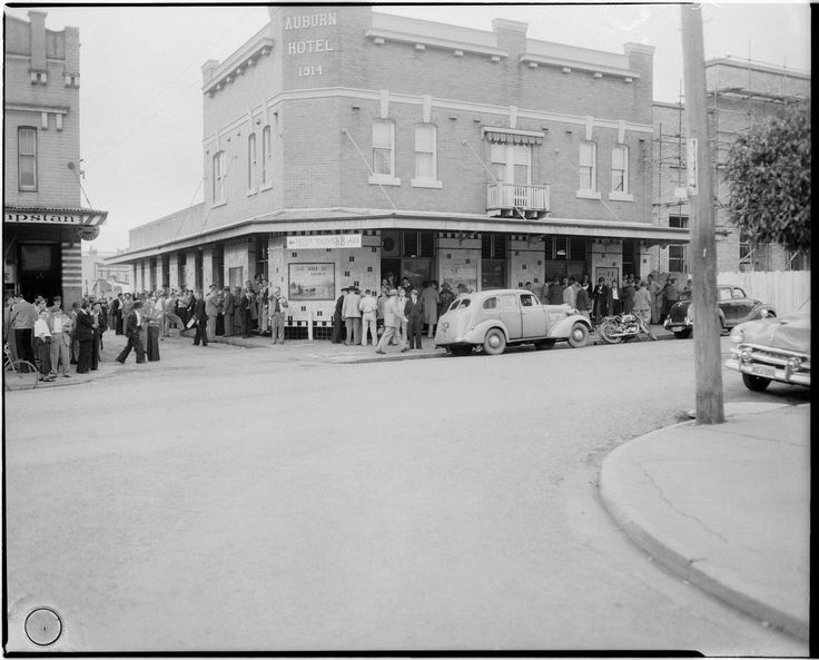 Auburn, NSW. Exterior view of the Auburn Hotel with men queuing outside for the Six O'clock swill, 1952.  (Early closing at 6 pm).