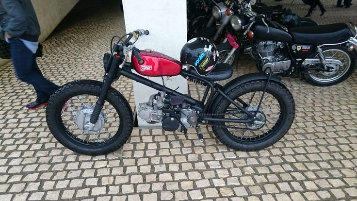 Custom moped with red tank, black rims and motorcycle tires
