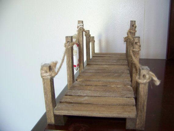 This Rustic Garden Nautical Bridge is a great addition to a Nautical Scene, Garden Pond, Fish Pond, Flower Garden, Fairy Garden, Gnome Garden. The Rustic Nautical Bridge is rough sawn and stained, with twine and wooden life preserver. It measures aprox 16 x 4-3/4 x 5. It will definitely be a conversation piece of home decor also