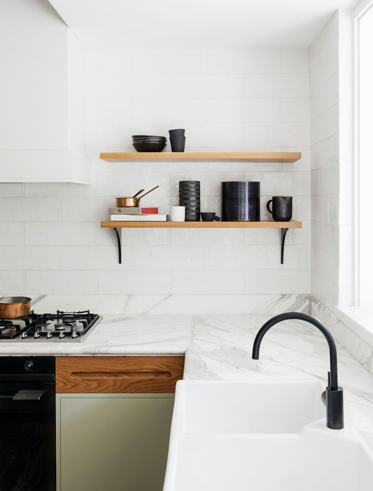 A clean and fresh-looking kitchen remodel with Calacatta marble counters, handmade subway tiles, a black spout faucet, and butler's sink by interior designers Arent & Pyke of Sydney. The cabinets are painted and feature custom oak panels. The open shelves have custom black brackets made of MDF   Remodelista