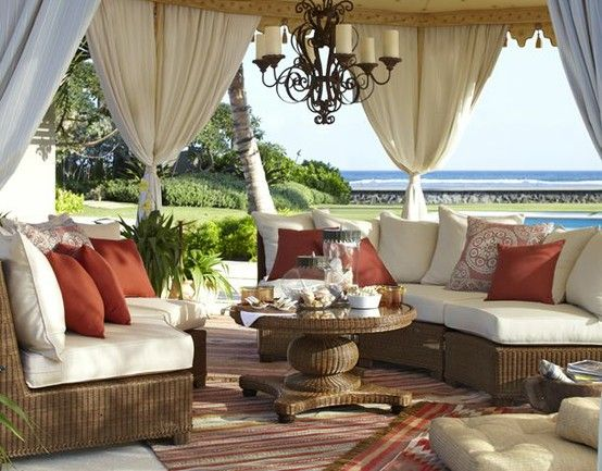 Outdoor patio with woven sectional seating and coffee table. Striped area rug, cabana style outdoor drapes and rustic candle chandelier.