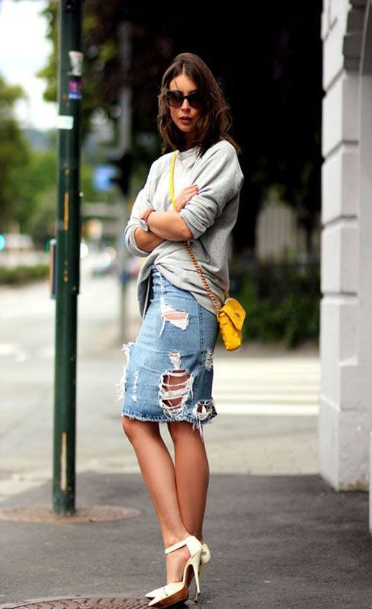 saia jeans rasgada lápis com moletom cinza, bolsa pequena amarela transversal e scarpin branco:
