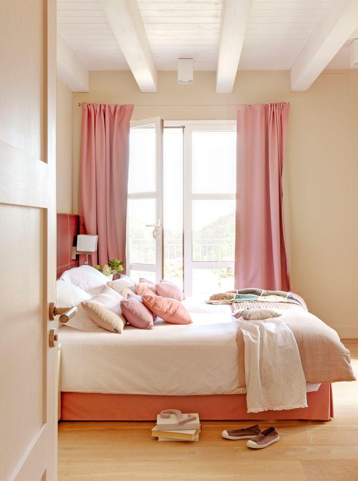 Dormitorio en tonos blancos con ropa de cama y cortinas rosa, cojines y ventana abierta_323358