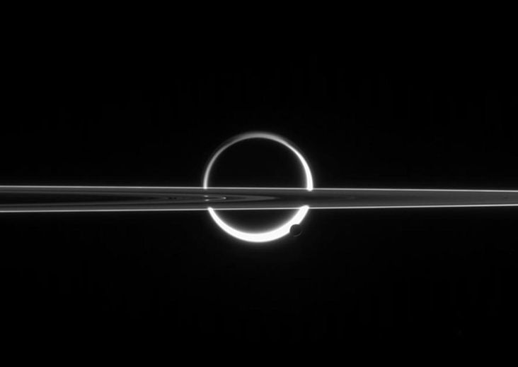 Saturn's rings cut across an eerie scene that is ruled by Titan's luminous crescent and globe-encircling haze, broken by the small moon Enceladus, whose icy jets are dimly visible at its south pole. North is up.