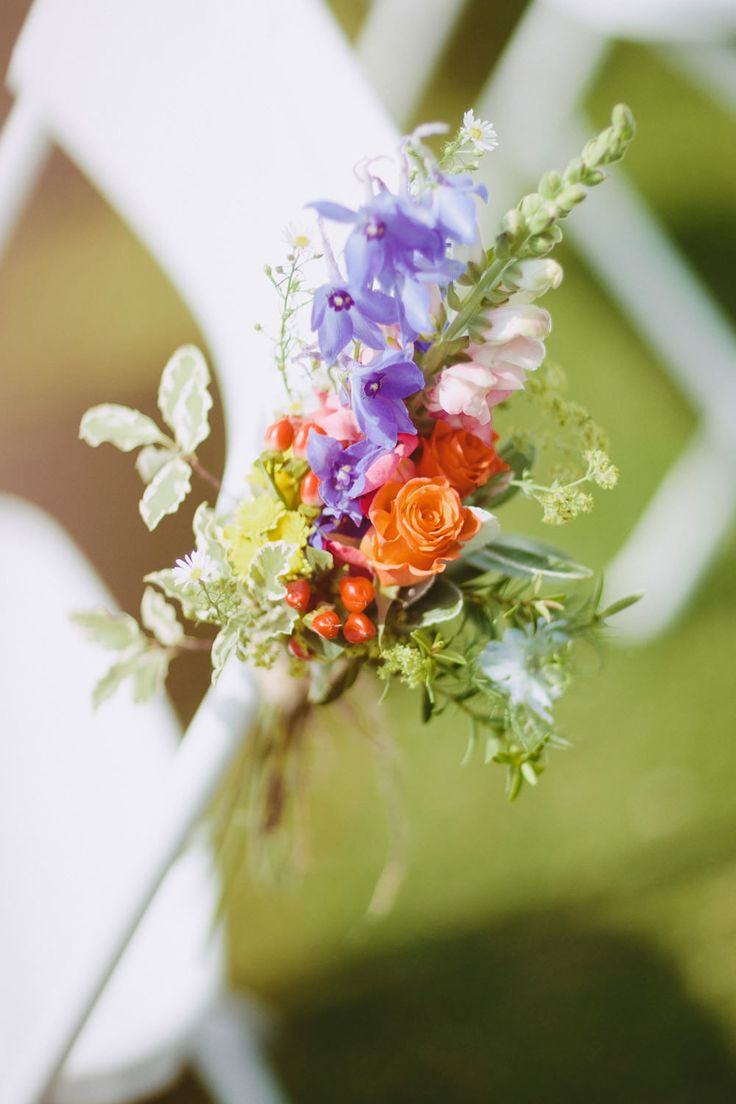 Brightly coloured flower posies on the aisle chairs - Image by David Jenkins - Stephanie Allin Bride And Maids To Measure Bridesmaids For A Scottish Castle Wedding At Wedderburn Castle With Groom In Tartan Suit