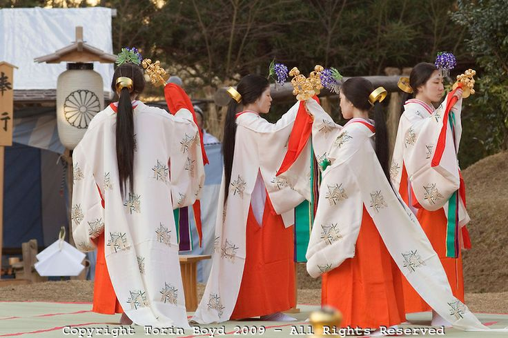 These are miko shrine maidens performing a special Shinto Shaden Kagura dance ritual during the annual On-Matsuri festival, a traditional Shinto religious festival held at the Kasuga Wakamiya Shrine in the ancient Japanese city of Nara, Japan. In older days, miko were considered shamans, but today they take on a more lighter role as priestesses or ceremonial duties.